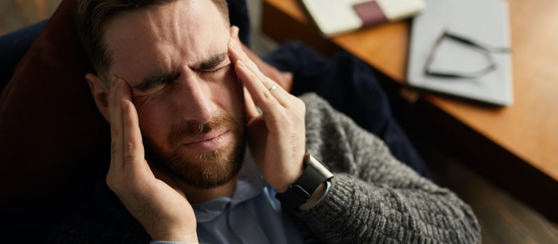 Young businessman has a headache he lying on the sofa and resting after work