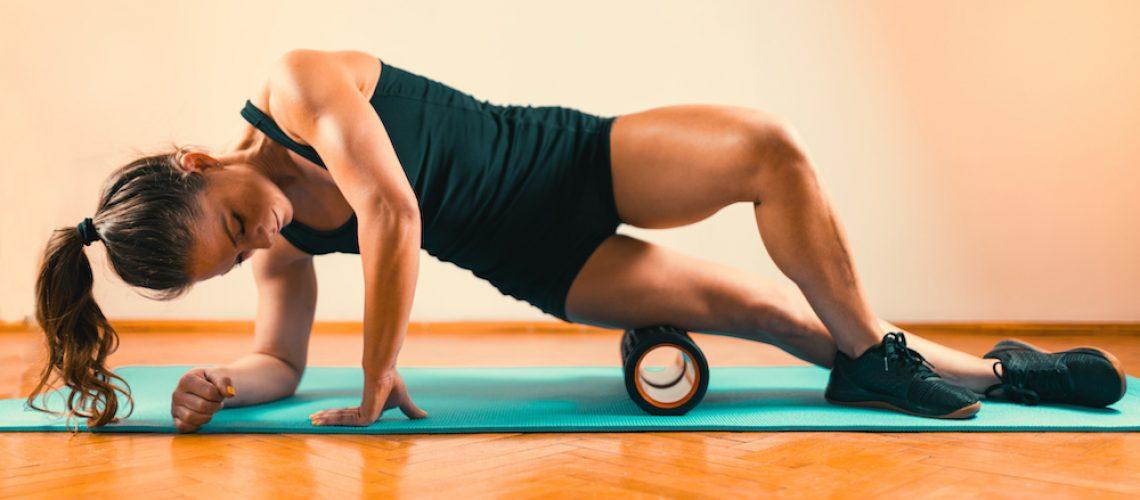 Sporty Woman Massaging Her Legs with Foam Roller